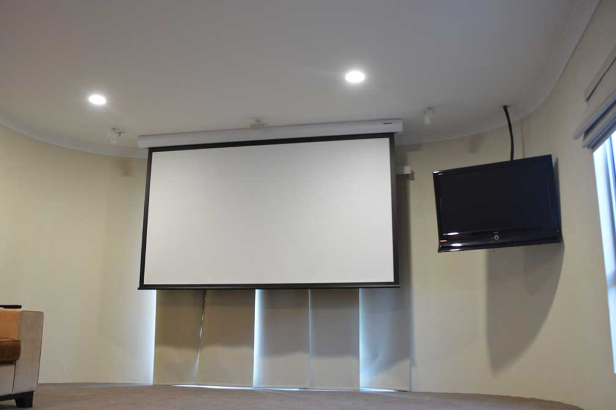 "Yeppoon Home – ScreenTechnics motorised 110"" screen, Optoma projector with secondary TV screen, Home Theatre system with Control4 automation."