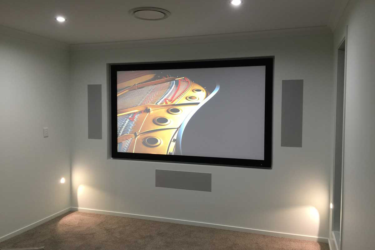 "Norman Gardens Home – Media Room with Epson projector and 92"" fixed screen and SpeakerCraft in-wall Home Theatre system."